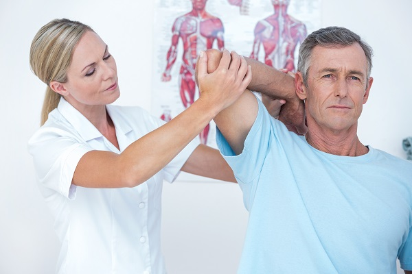 Woman physiotherapist treating a mans shoulder