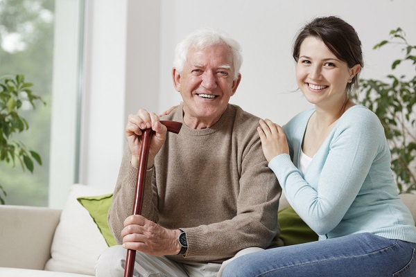 Woman seated next to an elderly man with a walking stick